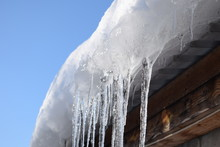 Beautiful Icicles Shine In Sun Against Blue Sky. Spring Landscape With Ice Icicles Hanging From Roof Of House.