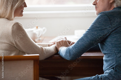 Canvastavla Cropped image middle aged couple sitting at table holding hands