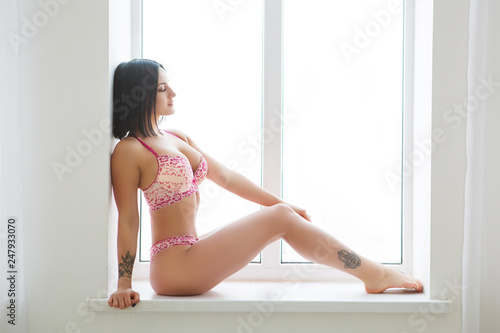 Sexy brunette beauty posing at the window. Sexy brunette female body lingerie.