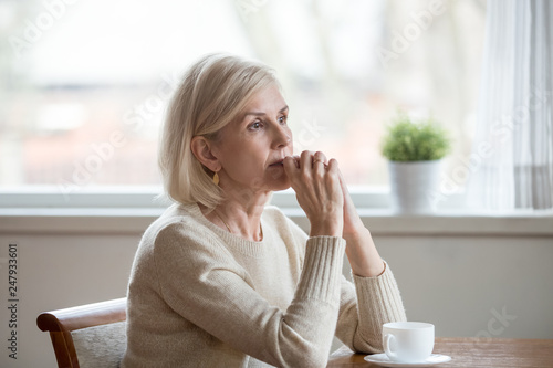 Fotografia  Thoughtful woman sitting at table with cup of tea