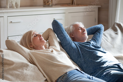 Fotografie, Obraz  Aged spouses lying on couch putting hands behind head