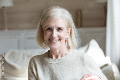 Fotografia  Smiling aged female sitting in living room looking at camera