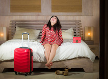 Young Beautiful And Happy Asian Chinese Woman Check In Luxury Hotel Room Relaxed And Cheerful In Elegant Chic Dress Playful On Bed With Luggage Enjoying Holidays