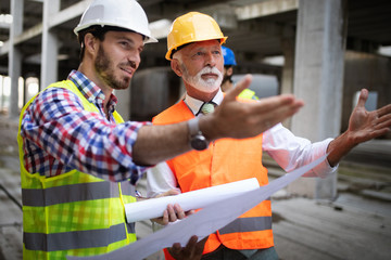 Obraz na SzkleTeam of architects and engineer in group on construciton site check documents and business workflow