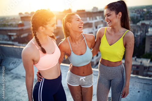 Fotografia  Group of young happy people friends exercising outdoors at sunset