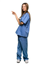 Full Body Young Nurse Pointing Finger To The Side In Lateral Position On Isolated Background