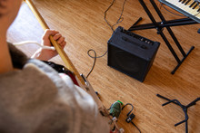 A Person Playing A Guitar And Using Effect Pedals In Private Studio Next To Synthesizer