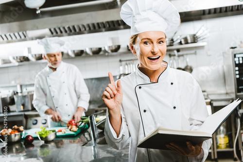 beautiful female chef in uniform holding recipe book and