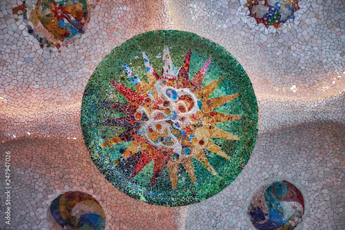 Round tile mosaic with sun on ceiling in the hall of hundred columns in the Barcelona Park Guell Canvas Print