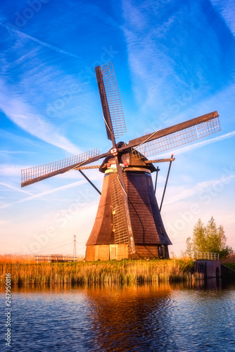 Amazing nature, scenic sunset landscape, windmills, blue sky and water. Traditional dutch countryside, famous village of mills Kinderdijk, popular tourist attraction in Netherlands (Holland). Vertical