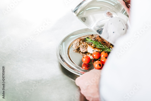 partial view of male chef holding dome from serving tray with meat dish in restaurant kitchen
