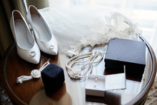 Luxury White Women Shoes, Veil, Golden Wedding Rings And Bride Jewelry (pearls Necklace, Bracelet And Earrings) On Wooden Table, Copy Space. Wedding Morning Preparation. Bridal Accessories