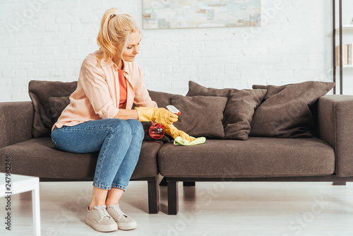 Fotografia  Senior woman in jeans cleaning sofa with spray and rag