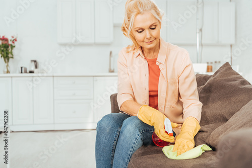 Fotografia  Senior woman in rubber gloves cleaning sofa with spray and rag