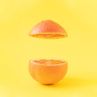 canvas print picture - Sliced red grapefruit with creative copy space on bright yellow background.