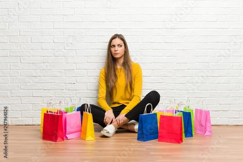Plakat Młoda dziewczyna z dużo torba na zakupy czuje spęczenie