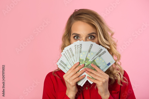 Fotografía  beautiful young girl in a red shirt with euros in hands on a pink background wit