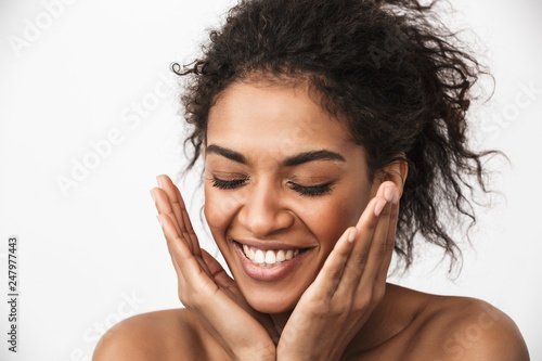 Valokuva  Happy young african woman posing isolated over white wall background