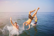 Young People Jumping Inside Ocean In Summer Excursion Day. Happy Crazy Friends Diving From Sailing Boat Into The Sea. Vacation, Youth, Travel And Fun Concept