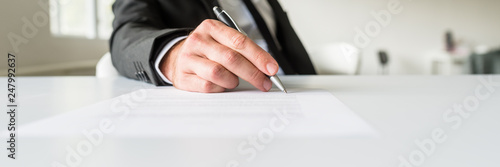 Obraz Wide view image of businessman sitting at his office desk signing a document - fototapety do salonu