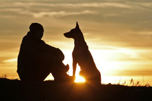 A Man And A Dog On The Background Of A Beautiful Sunset