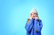Portrait of emotional young woman in stylish hat, sweater and mittens on color background, space for text. Winter atmosphere