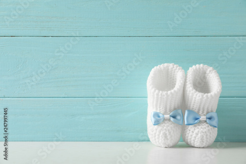 Fotografia, Obraz  Handmade baby booties on table against wooden background