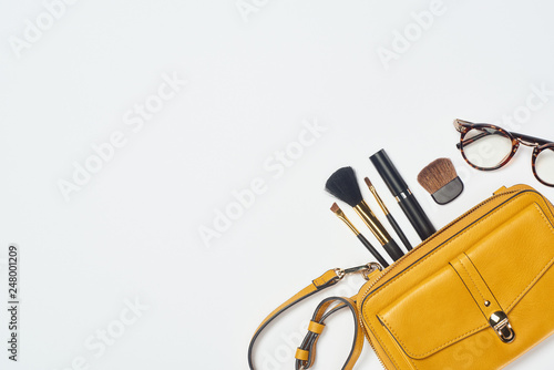 Glasses, mascara, cosmetic brushes and yellow bag on white background