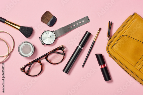 Top view of watch, bag, lipstick, glasses, eye shadow, bracelets, mascara and cosmetic brushes on pink background