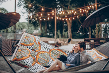 Romantic Hipster Couple Enjoy Rest On A Hammock At Park Resort, Cute Woman Lying With Handsome Man, Lights In The Background
