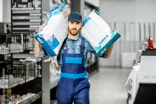 Fotografia, Obraz  Portrait of a handsome workman in blue overalls holding bags with construction m
