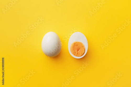 Single whole white egg and halved boiled egg with yolk on a yellow background Fototapeta