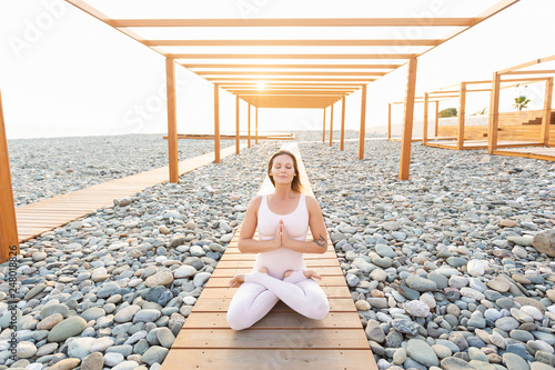 Fotografia  Graceful and flexible sporty young woman fitness or yoga instructor meditating a