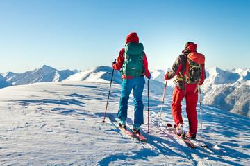 Skijaški muškarac i žena uživaju u pogledu na vrh u alpama.