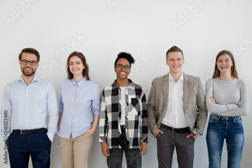 Fotografía  Diverse happy business people standing near wall looking at camera