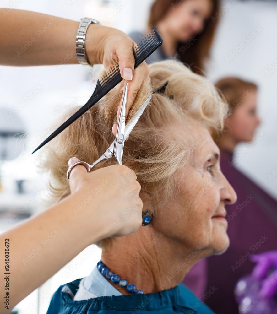 Fototapeta Closeup of senior woman getting haircut