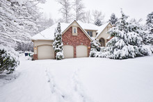 Suburban Home Blanketed In Snow With Footprints Leading To The Front Door And Around The Back