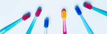 Composition Frame Of Colorful Tooth Brushes With Bright Color Bristles On A Light Pastel Blue Background. Long Wide Banner For Your Mock Up With Dental Tools And Empty Space For Text.