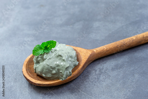 Fotografia  Wet French green Clay Powder for mask with aromatic mint leaves in wooden spoon