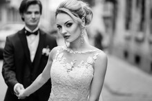 Stylish Bride And Groom Walking In City Street. Luxury Wedding Couple Holding Hands At Old Building In Light. Romantic Sensual Moment.  Woman Looking And Man Posing, Black And White