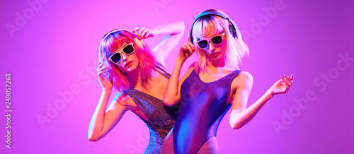 canvas print motiv - evgenij918 : Fashion. Two sexy DJ girl in Colorful neon light dance. Glamour party fitness woman with Dyed Hair in Trendy headphones. Young beautiful model enjoy nightlife. Creative art banner