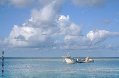Photo Stands Shipwreck White boat-wreck in the Maldivian sea under a sky with clouds