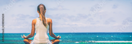 Fotografie, Obraz  Yoga meditation wellness woman meditating on morning sunrise beach background in peace and zen positive attitude panoramic banner