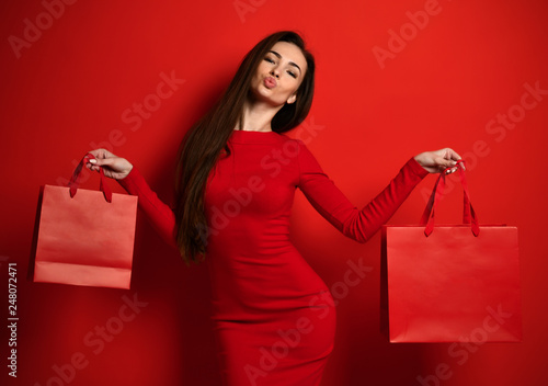 Fototapeta Woman in red tight dress holds two red shopping bags and holds lips like in a kiss obraz