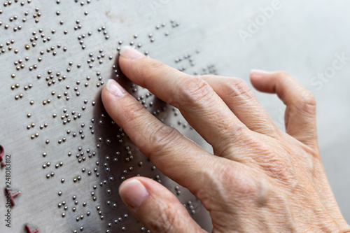 Photo Finger reading braille tactile on public park message board