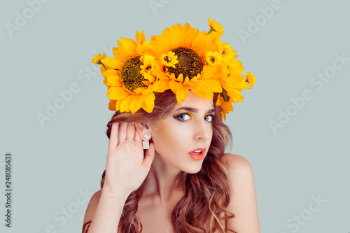 Woman with floral headband hand to ear listening in shock Canvas Print