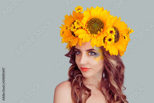 Fotografie, Obraz  closeup portrait, confident, successful, beautiful attractive young woman in floral crown from sunflowers, posing looking away to side smiling fashion girl, isolated on grey gray background wall