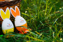 Handmade Funny Creative Eggs Lies On Green Grass Next To Natural Basket At Sunny Spring Day. Happy Easter! Egg Hunt, Decoration For Easter.