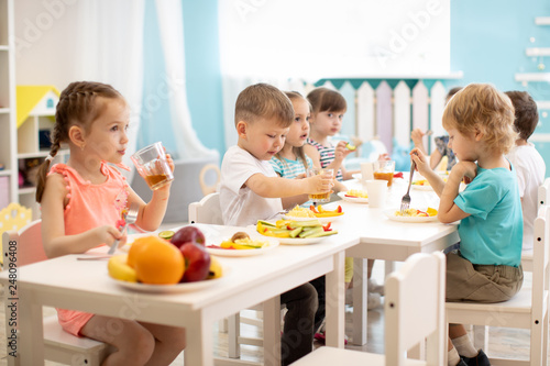 Fototapeta Group of children eating healthy food in day care centre obraz