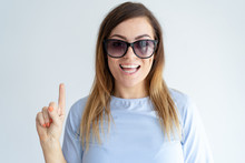 Cheerful Pretty Woman Pointing Upwards With Forefinger